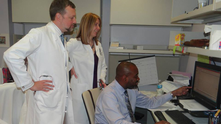 Patrick Coty, PA, having a discussion with his colleagues from the Pancreas Center